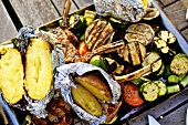 Barbecued vegetables, baked potatoes, lamb chops on barbecue tray