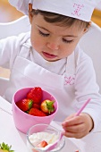 Little girl in chef's hat eating strawberries
