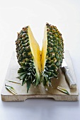 Pineapple, halved, on chopping board