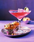 A red cocktail in a glass next to two muffins