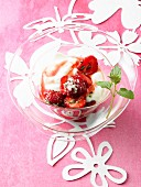 A glass bowl of strawberries and yogurt with rhubarb syrup