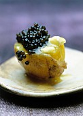A new potato with caviar on an old-fashioned plate