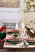 A Mediterranean themed table outside laid with wine and olives