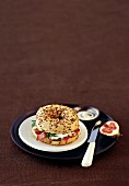 A ham and feta bagel served with figs on a brown plate