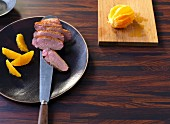 Sliced duck breast fillets being arranged on a plate with orange fillets