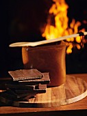 A stack of chocolate in front of a pot with an open fire in the background