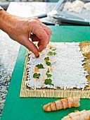 Sushi being prepared: sushi rice being spread on a bamboo mat and topped