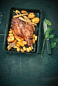 Braised leg of lamb with carrots, apples and potatoes in a roasting tin