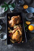 Braised guinea fowls with vegetables and oranges