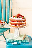 A layered sponge cake with cream and strawberries