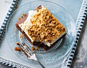 A slice of amaretto cake with cream and amarettini crumbs