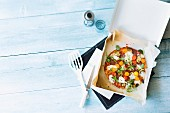 Wholemeal tomato-mozzarella pizza in a box (seen from above)