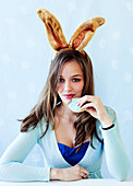 A woman wearing bunny ears eating a biscuit