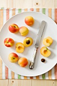 A plate of fresh apricots and a knife, whole and halved