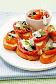 Crostini (toasted bread topped with tomatoes, Parmesan cheese and olives)