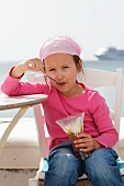 A little girl eating a chocolate ice cream sundae on a beach