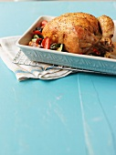 A whole roast chicken in a roasting tin