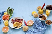A breakfast table laid with scrambled egg, salmon, jam, muesli and grapefruit