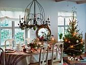 Festlich gedeckter Weihnachtstisch neben einem Weihnachtsbaum