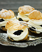 Profiteroles filled with cream and fresh blackberries on a silver plate
