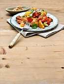 Chicken legs with corn cobs and tomato salad