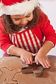 Little girl cutting out gingerbread men