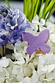 A purple butterfly biscuit, lilac and white hydrangeas