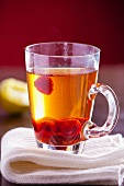A glass of jasmine tea with raspberries