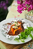 Baked sweet potato with chili butter in aluminum foil