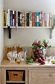 Autumnal ambience - cookery books above kitchen unit with bottles and fresh apples