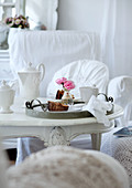 Breakfast crockery and small vase of roses on vintage tray on antique, white-painted table