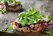 Open-faced sandwiches with ham, grilled aubergine, cheese and rocket