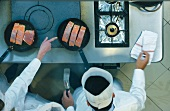 Chefs frying salmon fillets in a commercial kitchen