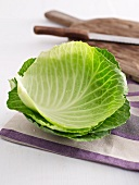 White cabbage leaves and a chopping board in the background