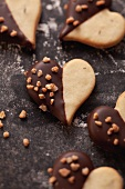 Heart-shaped biscuits decorated with chocolate icing and chopped nuts