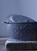An iron, oval-shaped baking dish with a lid