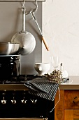 A kitchen counter with a cooker, pots and dried herbs