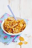 Cornflakes in a ceramic bowl with a spoon on a colourful napkin