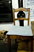 An old wooden chair with a checked cushion