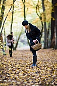 Two women collecting mushrooms in an autumnal forest