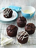 Chocolate muffins decorated with strips of icing sugar