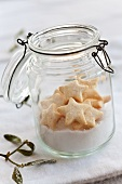 Sugar and star-shaped biscuits in a flip-top jar with a sprig of mistletoe