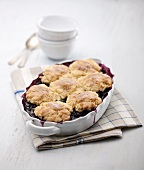 Blueberry Cobbler in Baking Dish; Serving Bowls and Spoons