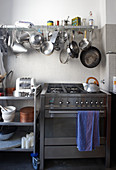Modern gas cooker with stainless steel front next to table on castors and below pots and pans hanging from wall-mounted shelf