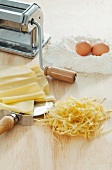 Homemade tagliatelle, a pasta maker, flour and eggs