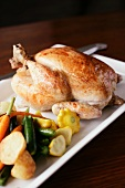 A whole roast chicken with a side of vegetables