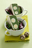 A spinach terrine with quail's eggs on a mixed leaf salad