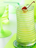 Tom Collins in a Green Striped Glass with a Straw, Ice and Maraschino Cherry