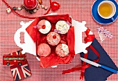Cupcakes with Union Jacks in a box and a cup of tea