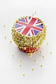 A cupcake decorated with a Union Jack and sugar balls